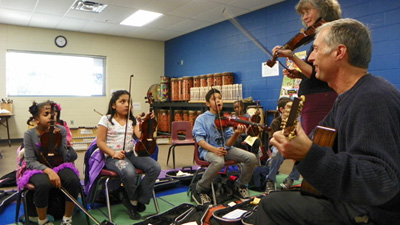 Music education student Mike Sorenson (right) works with a class at Owl Creek School in Fayetteville.